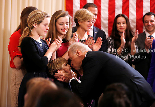 United States Vice President Joe Biden kisses members of his family after taking the oath of office during a swearing-in ceremony at the Vice President's residence at the Naval Observatory  in Washington January 20, 2013.  .Credit: Kevin Lamarque / Pool via CNP
