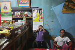 Posters of the King and Queen adorn every household. A roadside restaurant, cafe, shop in rural Punakha, Bhutan..Bhutan the country that prides itself on the development of 'Gross National Happiness' rather than GNP. This attitude pervades education, government, proclamations by royalty and politicians alike, and in the daily life of Bhutanese people. Strong adherence and respect for a royal family and Buddhism, mean the people generally follow what they are told and taught. There are of course contradictions between the modern and tradional world more often seen in urban rather than rural contexts. Phallic images of huge penises adorn the traditional homes, surrounded by animal spirits; Gross National Penis. Slow development, and fending off the modern world, television only introduced ten years ago, the lack of intrusive tourism, as tourists need to pay a daily minimum entry of $250, ecotourism for the rich, leaves a relatively unworldly populace, but with very high literacy, good health service and payments to peasants to not kill wild animals, or misuse forest, enables sustainable development and protects the country's natural heritage. Whilst various hydro-electric schemes, cash crops including apples, pull in import revenue, and Bhutan is helped with aid from the international community. Its population is only a meagre 700,000. Indian and Nepalese workers carry out the menial road and construction work.