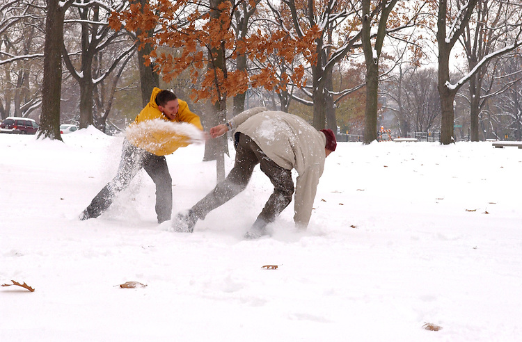 snow24_120502 --  Patrick O'brien and Chris Lewis, staffers from the Russell Senate Office Building enjoy a snow ball fight during the first snow storm of the winterin the upper senate park.