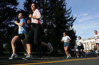 Sunlight illuminates the face ofrunners as they make their way through campus at the University of Virginia during the Charlottesville 10-miler Saturday in Charlottesville, Va. Photo/Andrew Shurtleff