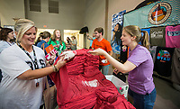NWA Democrat-Gazette/BEN GOFF @NWABENGOFF<br /> Tracy Reither (left), assistant to the principal at Bentonville High School, picks up her free T-shirt from Brittney Marstiller with Skyline Merch Friday, Aug. 9, 2019, during the Bentonville Teacher's Fair at Bentonville High School. Marstiller said that the company has given out 3,500 free shirts to teachers and staff at teacher's fairs this week in Northwest Arkansas. The Greater Bentonville Area Chamber of Commerce holds the event before the start of classes each year to give community businesses and organizations a chance to connect with the approximately 1,800 teachers and administrators in the Bentonville School District. Tuesday is the first day of class in Bentonville schools.