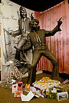 'ELVIS FANS', LIFE SIZE BRONZE STATUE OF ELVIS PRESLEY WITH FLOWERS & CARDS AT IT'S FEET, DEDICATED 'IN LOVING MEMORY', INSIDE THE SHOP 'ELVISLY YOURS' WHICH SELL MEMROBILIA OF THE STAR, LONDON