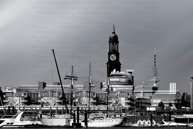A tram passes the Hamburg harbor with boats and sailing ships in Hamburg.
