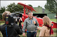 BNPS.co.uk (01202 558833)<br /> Pic: RobHenry/BNPS<br /> <br /> Local TV turned up to witness the maiden flight.<br /> <br /> The feared Fokker Dreidecker of the Red Baron has finally flown over Britian skies - after British based German doctor 'Baron' Peter von Brueggemann spent 9 years building a replica in his garage.<br /> <br /> The German GP based in Norfolk has spent 9 years building a Fokker triplane as a tribute to infamous WW1 Ace Manfred von Ricthofen, who terrorised the skies over the Western front during the first war.<br /> <br /> Dr Peter Brueggemann, 53, fufilled his childhood dream and emulated the notorious German fighter Ace when his hand built Dreidecker finally took off this week.<br /> <br /> Dr Brueggemann has even acquired the title Baron from the independent territory of Sealand so he can take to the skies as Baron Peter von Brueggemann in homage to his idol.<br /> <br /> The GP at the Holt Medical Practice in Norfolk finally reached for the sky at Felthorpe airfield near Norwich this week in front of nervous friends and family after thousands of hours spent crafting the aircraft.<br /> <br /> The father-of-two, who has lived in England with wife Sue for 20 years, has been taking flying lessons since his project began.