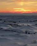 The snowy hills reflect the last light of the day as the sun sets over the Palouse of Eastern Washington State.