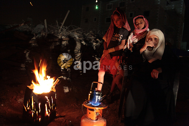 Palestinian children warm themselves by a fire outside their tent after Israeli forces destroyed their family house in the East Jerusalem neighbourhood of Beit Hanina, which falls in the West Bank side of Israel's separation barrier on Nov. 02, 2013. According to Israeli Authorities the house was built without a permit. Photo by Saeed Qaq