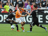 Houston Dynamo forward Brian Ching (25) goes against DC United midfielder Stephen King (7) right and midfielder Clyde Simms (19) left.   Houston Dynamo tied DC United 2-2, at RFK Stadium, Saturday June 25, 2011.