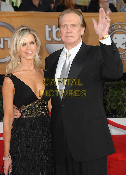 FAITH & LEE MAJORS.Arrivals at the 16th Annual Screen Actors Guild Awards Held At The Shrine Auditorium in Los Angeles, California, USA..January 23rd, 2010 .SAG SAGs half length married husband wife black suit jacket hand palm waving plunging neckline dress feathers .CAP/RKE/DVS.©DVS/RockinExposures/Capital Pictures
