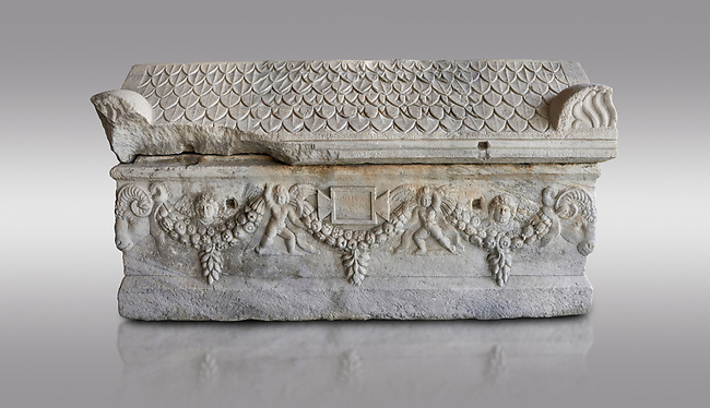 Roman relief sculpted garland sarcophagus with pitched tile sculpted roof, 3rd century AD. Adana Archaeology Museum, Turkey. Against a grey background