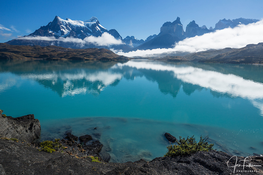 Clearing fog over Lago Pehoe. A few low clouds remain, obscuring the bases of Paine Grande and the Cuernos del Paine.  The still waters of the lake provide a mirror-like reflection of the peaks. Between Paine Grande on the left and the Cuernos is a view up the French Valley with the Shark's Fin and White Throne at the head of the valley.  Torres del Paine National Park, Patagonia, Chile.  A UNESCO World Biosphere Reserve.