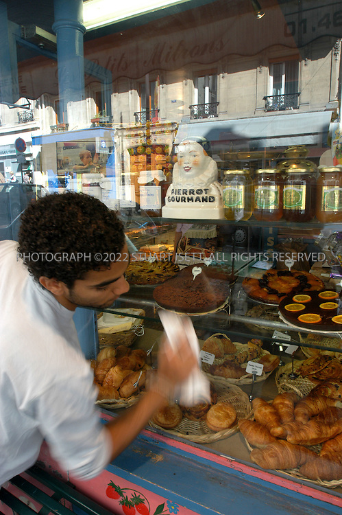 9/19/2004--Paris, France.An employee cleans the front windon of the 'Les Petits Mitrons' patisserie, on Rue Lepic, near the Hotel Utrillo on 7, Rue Aristide Bruant, in Paris' 18th arrondissemement...Photograph by Stuart Isett.©2004 Stuart Isett