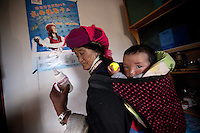 "April 30th 2011_Shangri-La, Yunnan, China_ Views of an ethnic Tibetan family in their traditional Tibetan farmhouse, in the tiny village of Rime, near the town of Zhongdian (or Shangri-La) in northern Yunnan province, China.  This family is one of several local families taking advantage of ""Home Stays,"" by opening their homes to visiting tourists.  Photographer: Daniel J. Groshong/The Hummingfish Foundation"