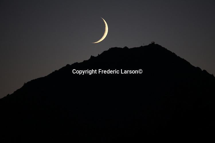 The crescent moon set behind Mount Tamalpais during twilight as seen from San Rafael, CA.