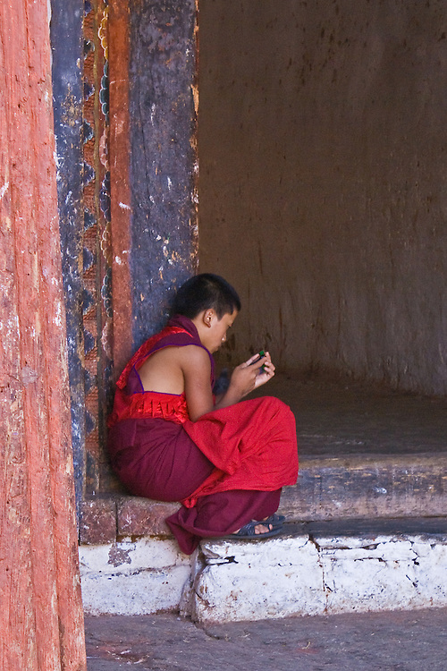 Young monk in traditional garb quietly secreted on a step to a long hallway playing with his Game Boy at the Chimi Lakhang Temple, Bhutan.