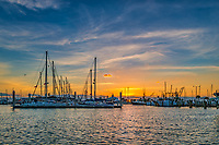 Sunrise over the Marina - We took this photo of the sunrise over the marina in Corpus Christi Texas.  The sunrise was just peaking up and gave a nice pink/orange glow over the water of the bay and just a hint of light over the sailboats and other boats dock in the marina.