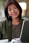 Asian woman wearing headset, working on laptop