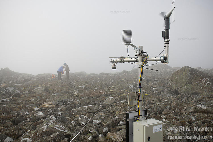 A weather station sits in the clouds while two figures work on scientific measurements for climate change studies.