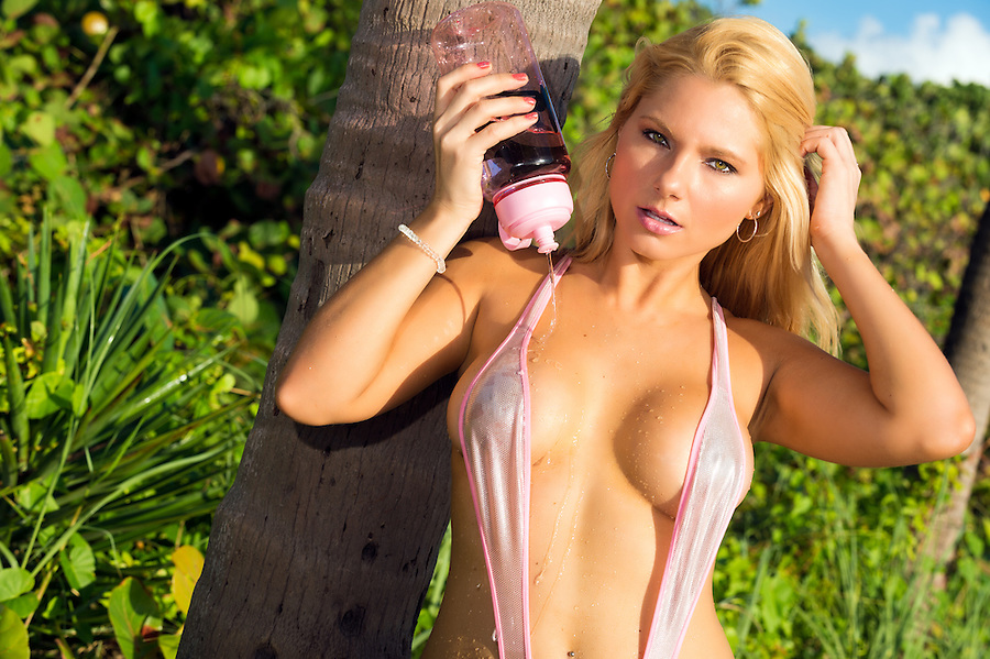 Seductive blond woman posing and pouring water over her body