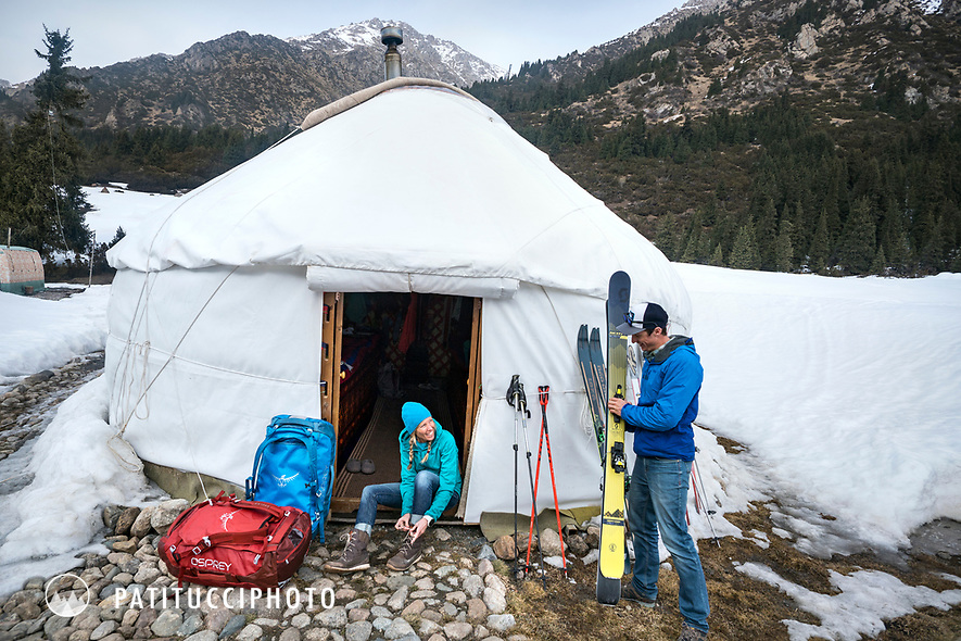 Two skiers arrive at a yurt with their duffel bags in the Kyrgyzstan backcountry while on a ski touring trip