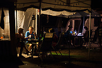Switzerland. Canton Ticino. Tenero. Camping Campofelice. Electric lights at nighttime. People play cards or talk together in the evening hours. A caravan, travel trailer, camper or camper trailer is towed behind a road vehicle to provide a place to sleep which is more comfortable and protected than a tent. It provides the means for people to have their own home on a journey or a vacation. Campers are restricted to designated sites for which fees are payable. 20.07.2018 © 2018 Didier Ruef