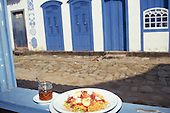 Paraty, Brazil. Plate of food, hot pepper oil on a windowsill with colonial cobbled street behind. Rio de Janeiro State.