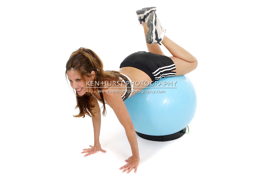 Beautiful brunette woman in a fitness workout using an exercise ball.  Shot isolated on white background.
