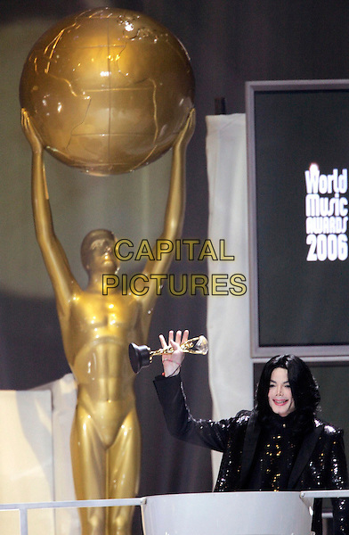 MICHAEL JACKSON .Michael Jackson dies at the age of 50 after suffering a heart attack on July 25th, 2009 .World Music Awards, Earls Court, London, England..November 15th, 2006.half length black jacket podium speech arm in air award trophy .CAP/PPG/JH.© Jens Hartmann/People Picture/Capital Pictures