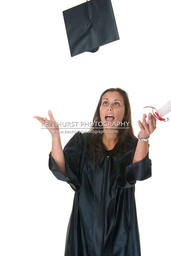 Very happy and proud beautiful young woman standing in graduation robes, cap and gown smiling holding her degree or diploma and throwing her cap in the air. Some motion blur from all the action.