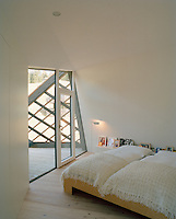 The angular bedroom opens through a matching shaped window onto a balcony