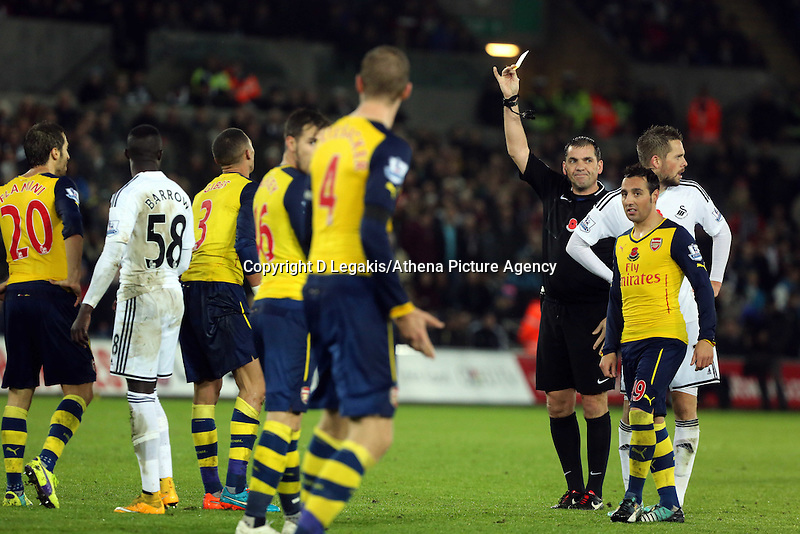 Sunday 09 November 2014 <br /> Match referee Phil Dowd shows a yellow card to Kieran Gibbs of Arsenal (3rd L) for his foul against Modou Barrow of Swansea<br /> Barclays Premier League, Swansea City FC v Arsenal City at the Liberty Stadium, Swansea, Great Britain. EPA/Dimitris Legakis