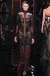 """Model walks runway in a jet black and blue embroidered long sleeve dress with saffron underlay from the Reem Acra Fall 2016 """"The Secret World of The Femme Fatale"""" collection, at NYFW: The Shows Fall 2016, during New York Fashion Week Fall 2016."""