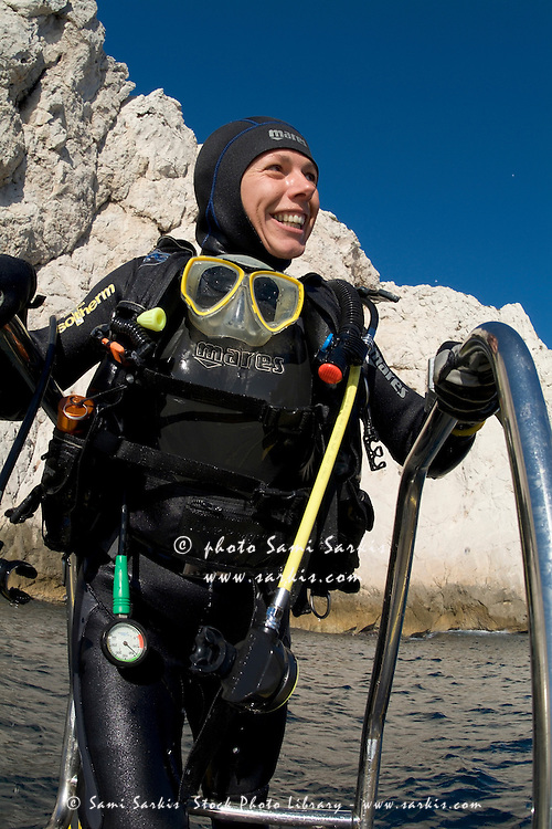 Female scuba diver climbing onboard a boat after diving, Maire Island, Marseille, France.