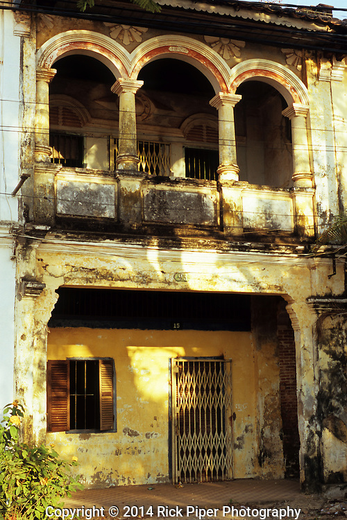 Weathered decaying arched facade and balcony of old French colonial building on the riverfront road, Kampot, Cambodia.
