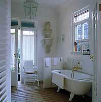 A bust is mounted on the wall above the loo which is shielded from the bath by a small folding screen