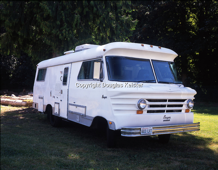 "This 26-foot 1972 Krager motorhome was built by the Krager Company in Winona, Minnesota. Winona's other claim to fame is that it is the birthplace of actress Winona Ryder. Like Ryder, whose family moved to Petaluma, California, when she was a small child, the Krager motorhome's tenure in Winona was very brief. At most, there were a few dozen units manufactured under the name Krager Kustom Koach, but despite their limited numbers they are very easy to spot thanks to their unusual front end. The modestly proportioned vehicle was powered by a generous 392 V8 International ""Cornbinder"" engine. The Krager's short wheelbase, high center, and noncorrosive fiberglass body made it more adaptable to backcountry roads than other bulky motorhomes. These qualities were meant to appeal to outdoorsmen and hunters. The unit was fully self-contained and was equipped with sleeping accommodations for four adults in bunk beds, rather than the standard two double beds. This lodging style definitely appealed to manly outdoorsmen. The Krager is owned by James Weaver Jr. Photographed at the Deming Log Show Grounds, Bellingham, Washington."