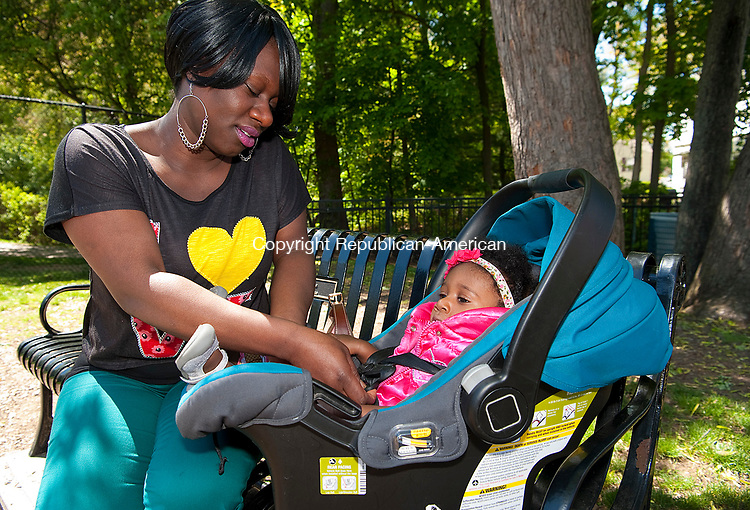 WATERBURY,  CT-051217JS17- Tamela Bennett of Waterbury, spends time with her 9-month-old daughter Shaniya, while her son Jaidyn, 8, plays nearby during a visit to Schofield Park in Bunker Hill section of Waterbury on Friday. <br /> Jim Shannon Republican-American
