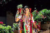 Colorful historical dancers in traditional dress with flowers in Oaxaca Mexico.