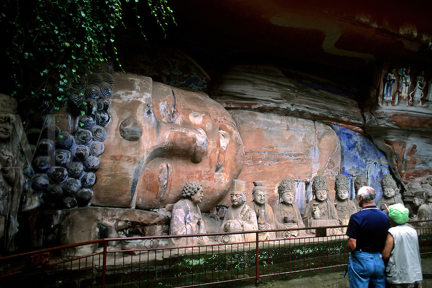 Tourists at stone carvings of Baobing Buddha Pilgrims at Dazu in China