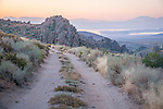 A twin-track dirt road goes through the cowboy rocks and Mono Lake in the early morning, Mono Basin, Calif.