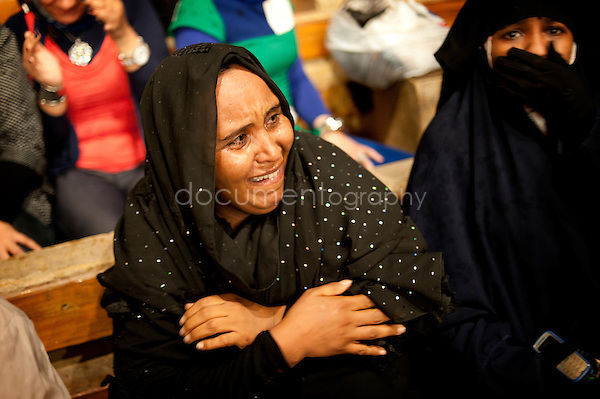 A woman in tears, frightened and in trance when Father Samaan approaches to her while throwing holy water on the crowd.<br />
