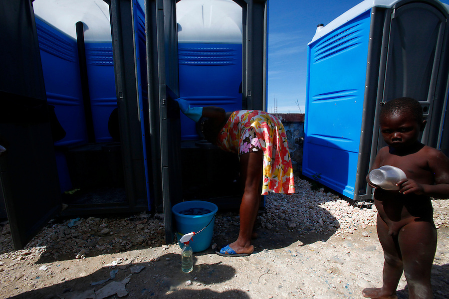Nov 10, 2010 - Port-au-Prince, Haiti.A local resident of the Cite Soleil area of Port-au-Prince, Haiti cleans a portable toilet inside one of many tent cities in the area on Wednesday, November 10, 2010 as fears of a Cholera outbreak spread through the area just two days after cases of the infection were confirmed in the area, the poorest slum in Haiti's capital. Officials from the Pan American Health Organization warn that Haiti's cholera epidemic, spread primarily through consuming infected water and food, is likely to grow much larger in the wake of Hurricane Tomas.  (Credit Image: Brian Blanco/ZUMA Press)