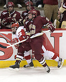 Ben Smith 12 of Boston College hits Ben Street 22 of the University of Wisconsin in front of the BC bench (Rooney, Bradford). The Boston College Eagles defeated the University of Wisconsin Badgers 3-0 on Friday, October 27, 2006, at the Kohl Center in Madison, Wisconsin in their first meeting since the 2006 Frozen Four Final which Wisconsin won 2-1 to take the national championship.<br />