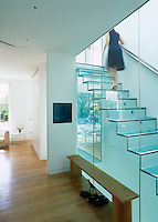 Home owner Emma Shapero ascends the glass staircase in the centre of her contemporary London home