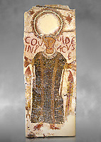 "5th century Eastern Roman Byzantine  funerary mosaic from Tarbaka in the Roman province of Africa Proconsularis , present day Tunisia, with a crown at the top probably a Christogram  (Latin Monogramma Christi ) is a monogram used as an abbreviation for the name of Jesus Christ, with a figure below and a latin text for the deceased "" Covuldeus in peace"". Either side of the figure are a lit candle which symbolises eternal faith. The Bardo National Museum, Tunis Tunisia. Against a grey art background.<br />