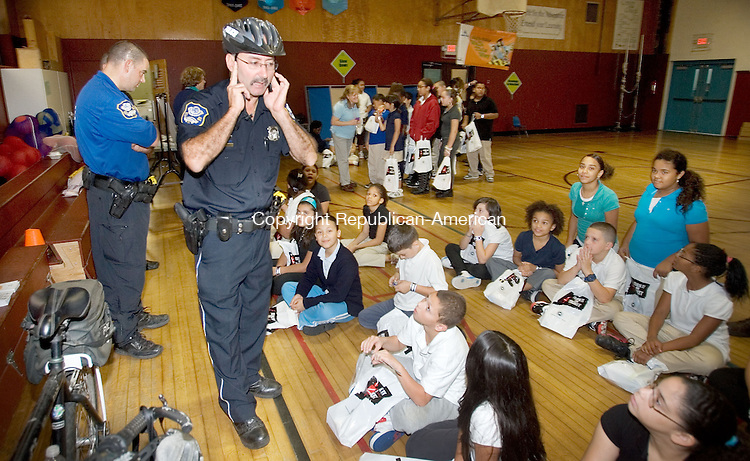 WATERBURY, CT. 06 October 2010-100610SV01--Bike Officer Neil Crespo shows the proper way to wear a bike helmet during a presentation to a 5th grade class at Driggs School in Waterbury Wednesday. Police officers from the community relations division were participating in a program called International Walk Your Child to School Day. .<br /> Steven Valenti Republican-American