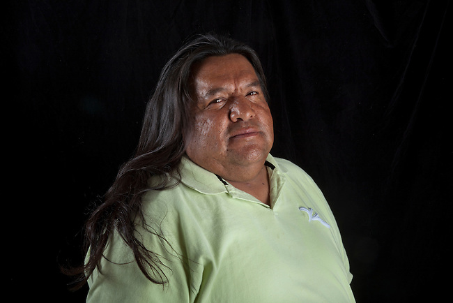 Contemporary Native American man with long hair poses next to black backdrop