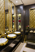 A luxurious mansion dazzles with gilded details and abundant use of marble. Serving the formal dining room, a guest bathroom in harmony<br />