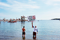 "A Greasy Pole Contest participant holds a sign reading ""It's not easy being greasy"" before the Saturday contest during St. Peter's Fiesta in Gloucester, Massachusetts, USA."
