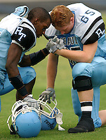 Ribault High School football players William Lewis and #65 Drew McMahon display sportmanship, faith and comradery as they pray together prior to the start of their game.