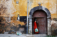 Woman on her way back from shopping, holding a green plastic bag full of goods (the same is in street as garbage plastic bag), old city , Portuguese Fortified city of Mazagan, El Jadida, Morocco. Picture by Manuel Cohen